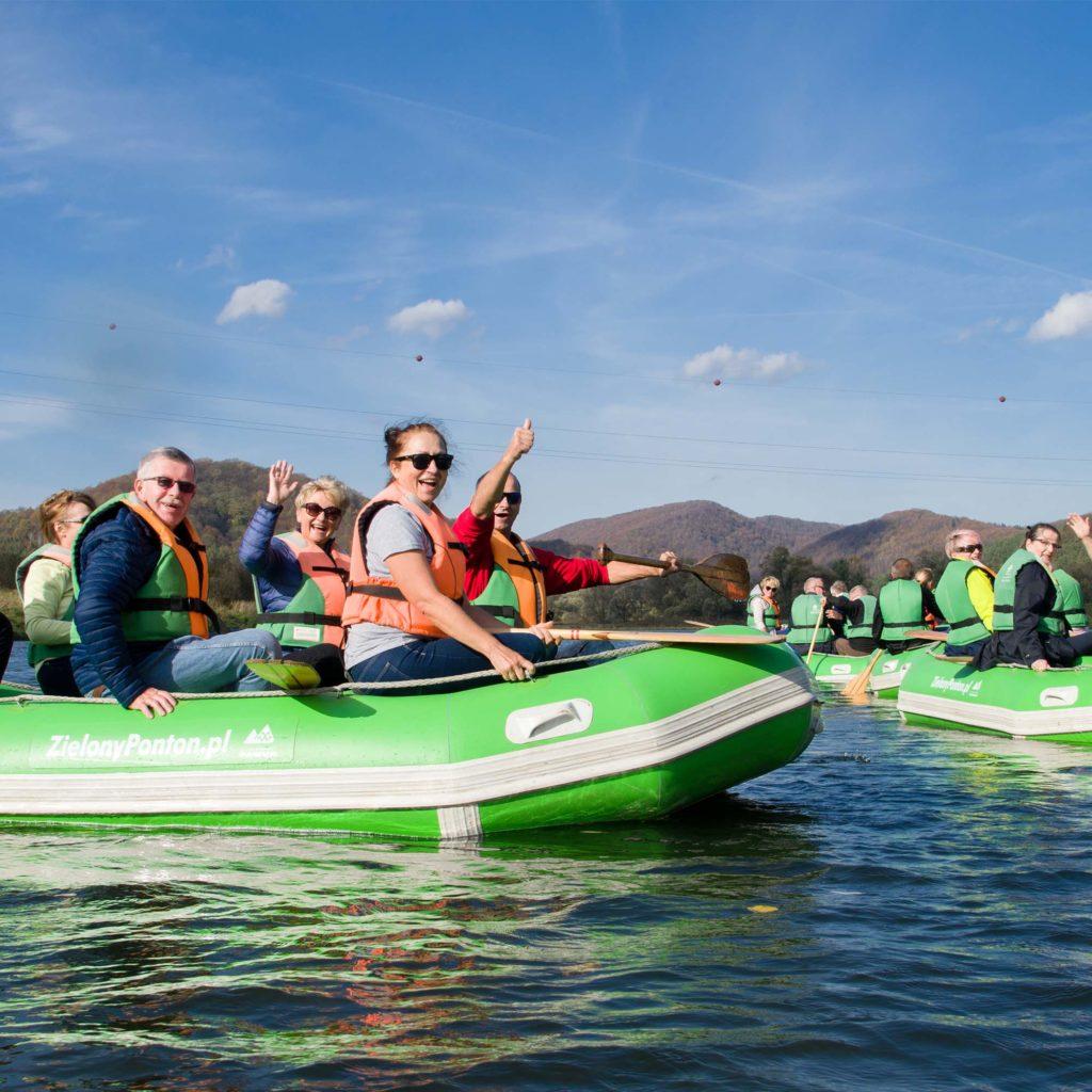 Uśmiechnięta i machająca grupa na pontonie.